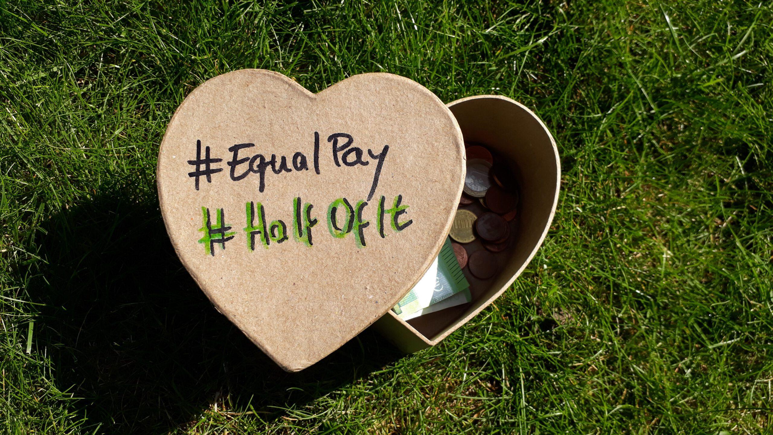 Foto mit einer Herzförmigen Kiste, die im Gras liegt und auf der #Halfofit und #EqualPay steht