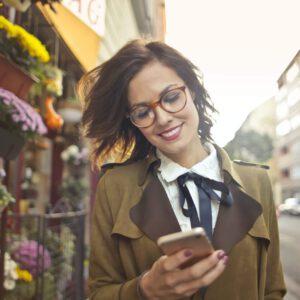 Eine Frau läuft die Straße entlang, hält ihr Handy in der Hand und schaut darauf. Im Hintergrund ein Markt.