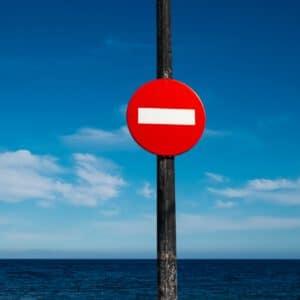 Foto eines Stoppschilds, dahinter blauer Himmel.
