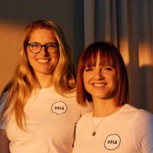 Die beiden Gründerinnen von ooia stehen nebeneinander und lächeln in die Kamera.